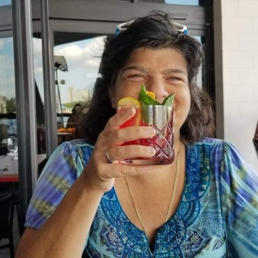 Cheryl Echevarria holding glass with Sangria in it.
