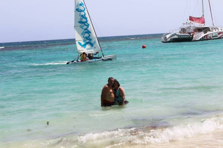 Cheryl and Nelson in water in front of Sandals Sail Boat. We are at the Sandals Ochi Beach Resort